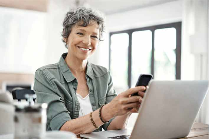 Lady using laptop and phone smiling