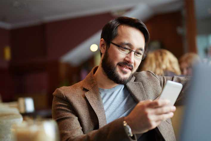 Man browsing website on mobile while in a cafe